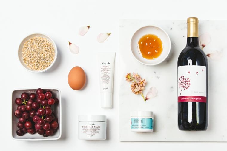 Ingredienti in ciotole, piatto con uva rossa, miele in piatto accanto ad una bottiglia di vino