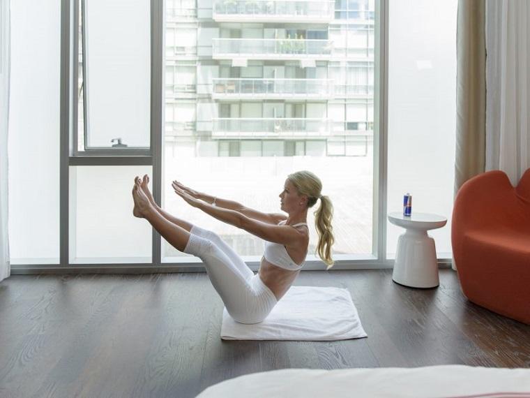 Esercizi da fare a casa, donna che si allena sul tappetino, allenamento gambe e addominali
