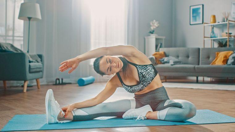 Scheda allenamento per aumentare massa muscolare a casa, donna sul tappetino che fa stretching