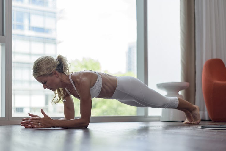 Donna che si allena in posizione plank, allenamento a casa, esercizi da fare sul pavimento di legno