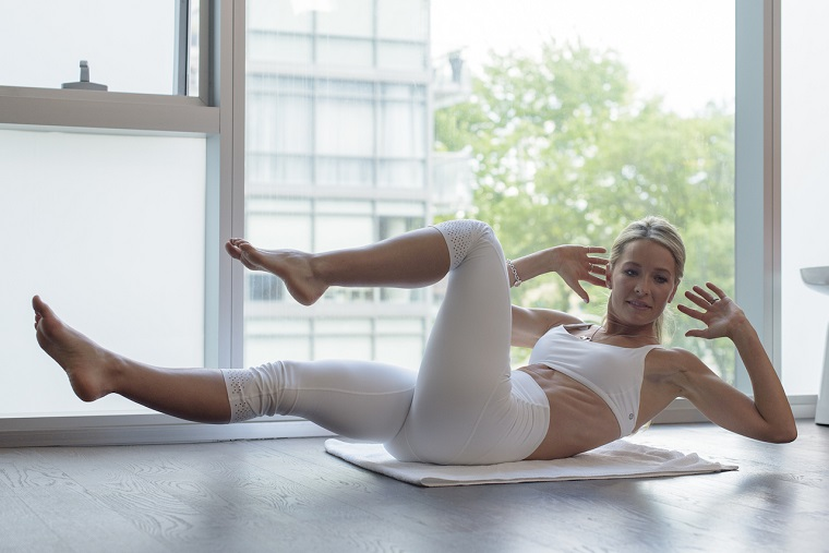 Allenamento completo a casa, donna sul tappetino che allena gambe e braccia