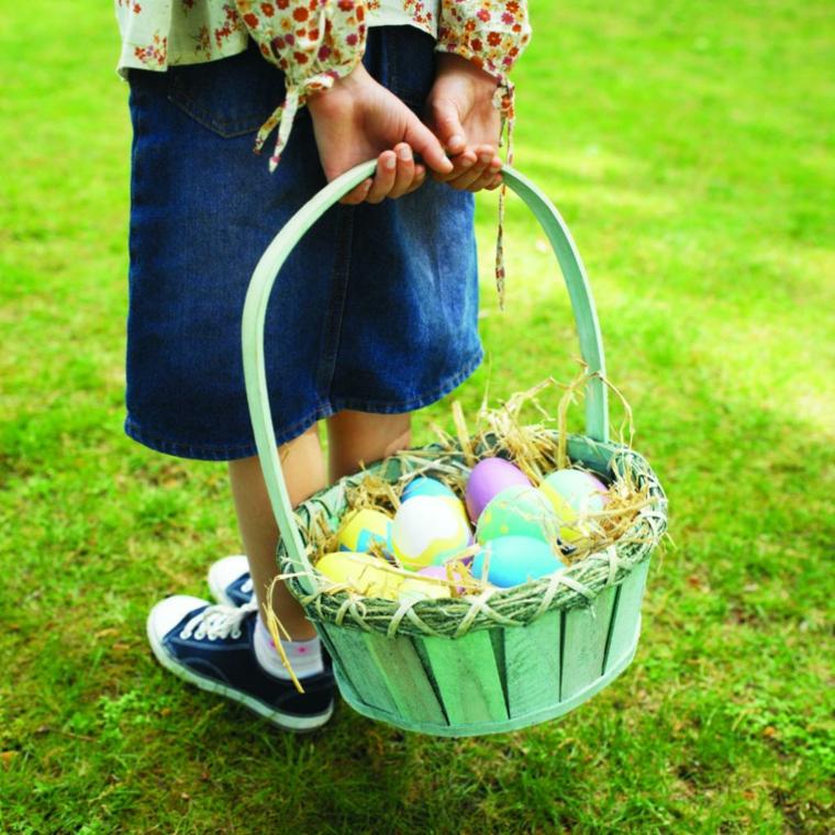 Frasi auguri di Pasqua simpatici, foto di una bimba con cesto di uova colorate