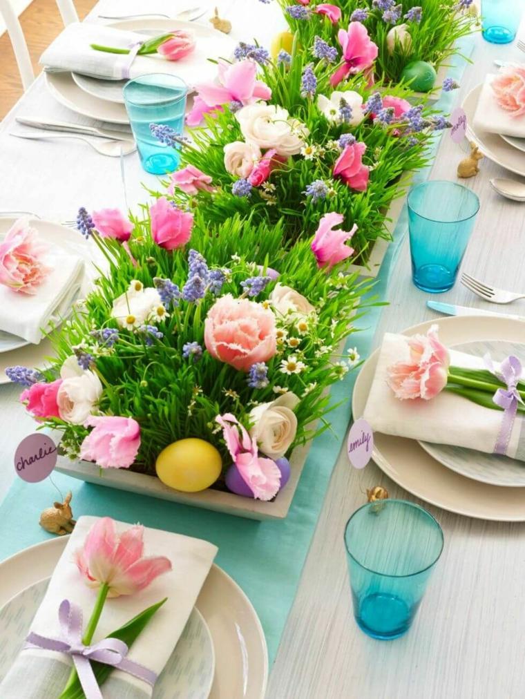 Foto di un centrotavola con uova pasquali e fiori, segnaposto con fiori e tovagliolo