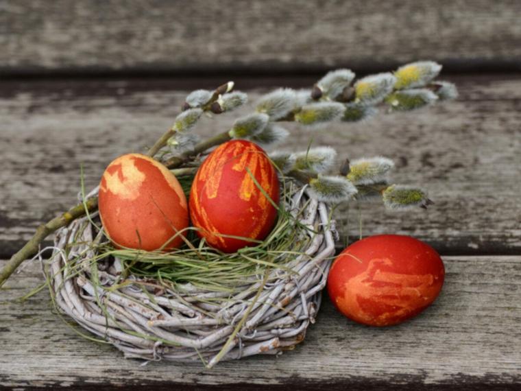 Foto di un cestino di rametti con uova pasquali colorate, tavolo con lastre di legno