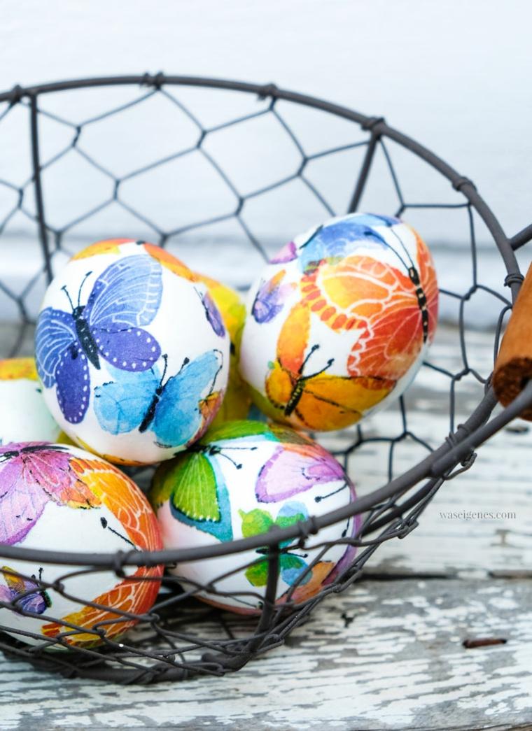 Foto di un cesto di metallo con uova pasquali dipinte, uova con disegno di farfalle