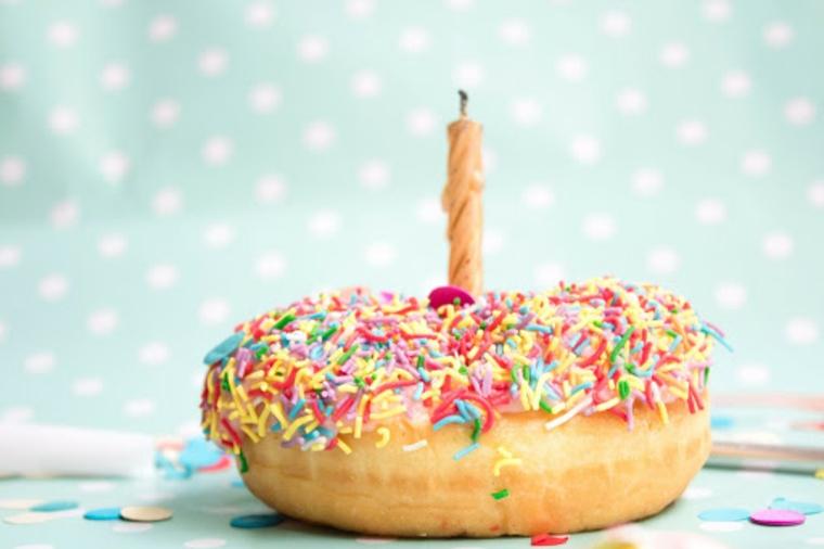 Foto di una ciambella colorata con candela, immagini di buon compleanno