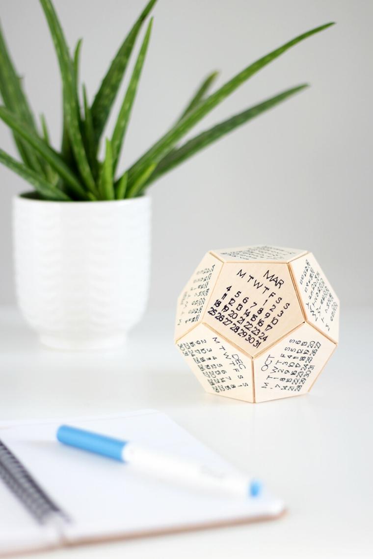 Idee regalo fidanzato, scrivania con vaso di aloe vera, calendario su foglio di legno