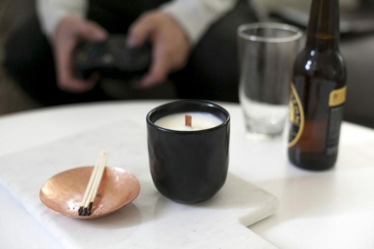 Sorprese anniversario, tavolo con candela fai da te in tazza accanto a fiammiferi