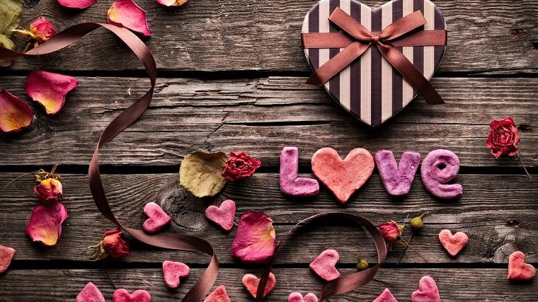 Scatola regalo con nastro a forma di cuore, tavolo di legno con foglie di rosa, idee regalo fidanzato