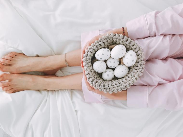 Foto di una donna in pigiama con cestino di uova, uova pasquali con disegni