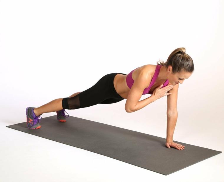 Allenarsi a casa donne, donna che esegue esercizio di plank sul tappeto