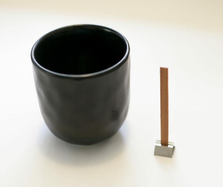Stoppino di legno accanto ad una tazza di porcellana, regali per lui romantici
