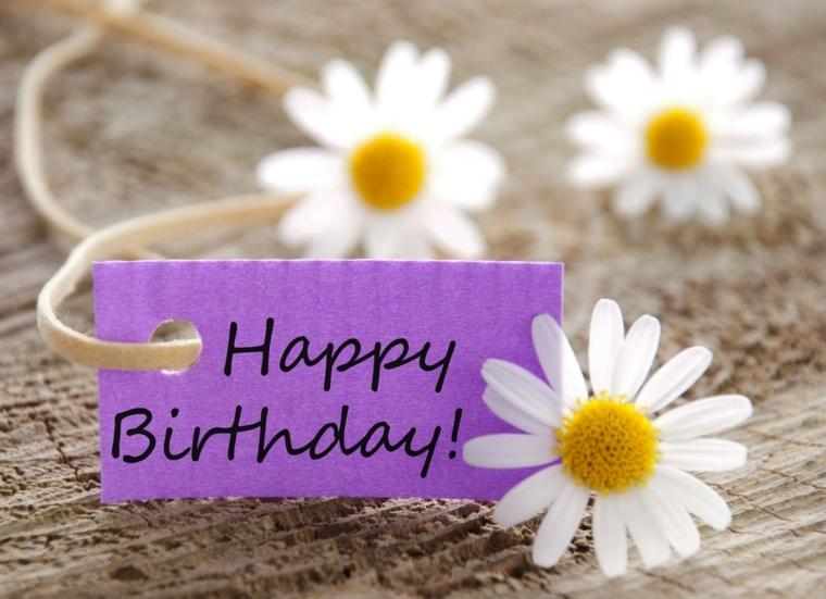 Come augurare buon compleanno, bigliettino viola con scritta e foto di margherite