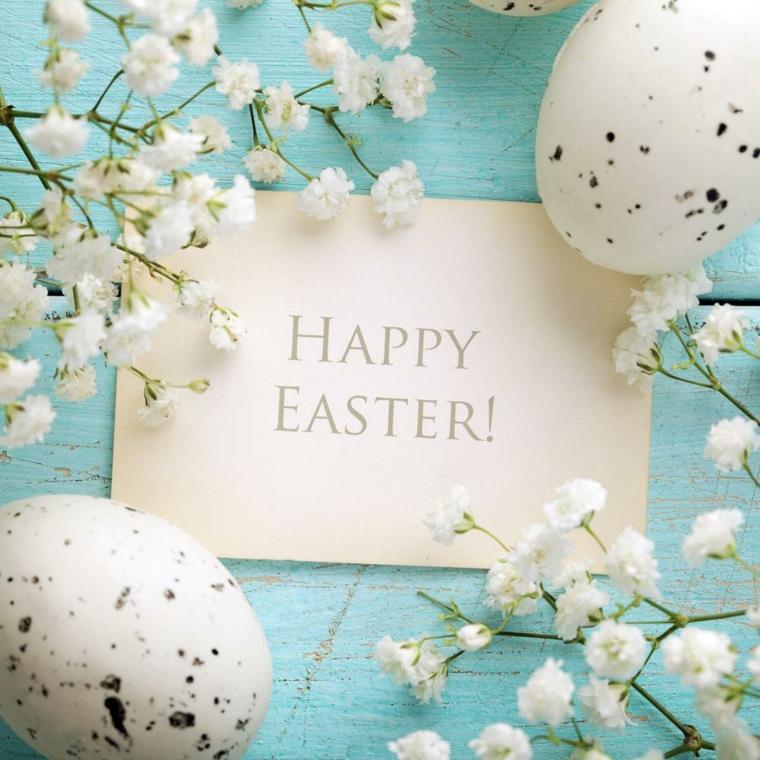 Foto di rami fioriti su uno sfondo blu, bigliettino con scritta Happy Easter, frasi auguri di Pasqua simpatici