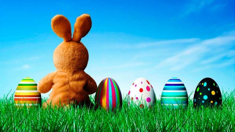 Foto di un peluche coniglio e uova pasquali colorate, foto di un prato con erba verde