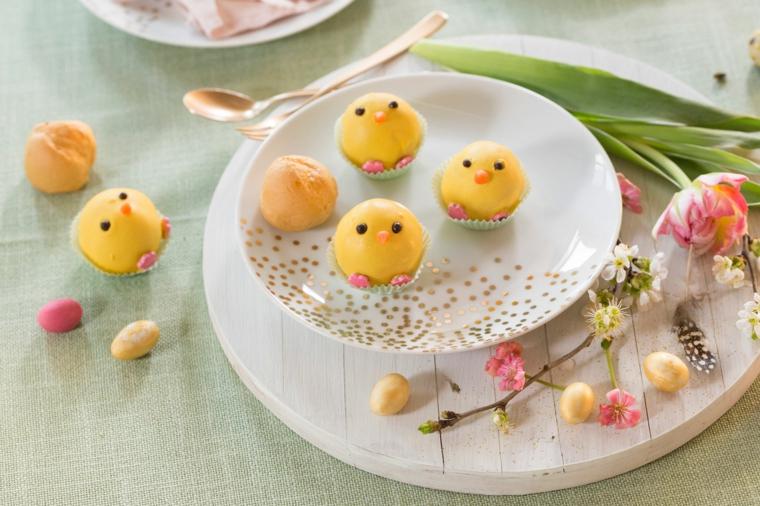 Piatto con uova decorate, tagliere di legno con ramo fiorito, immagine bella pasquale