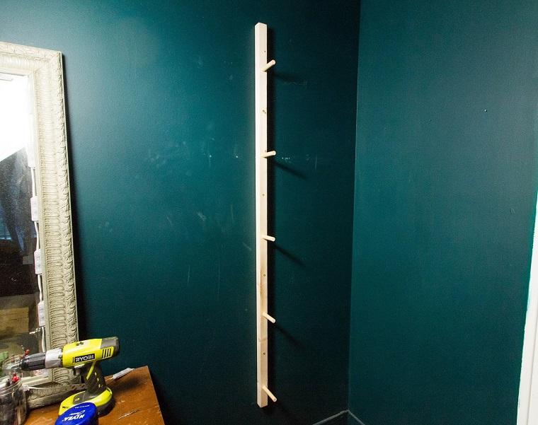 Idee scarpiera fai da te, lastra di legno con ganci attaccata ad una parete blu
