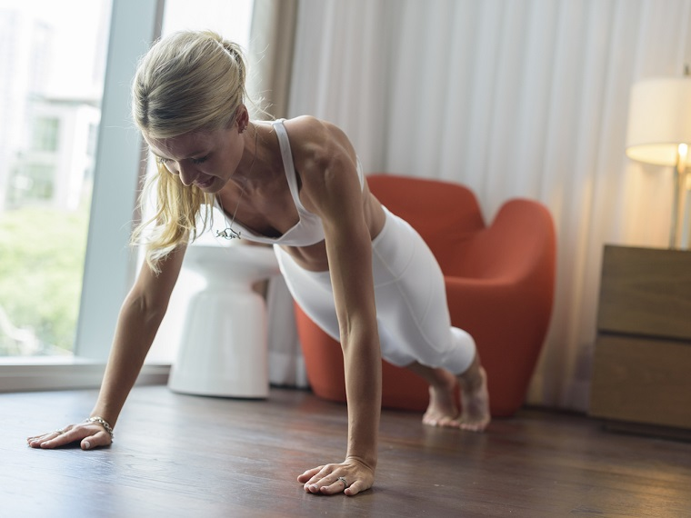 Esercizi gambe corpo libero, donna che fa le flessioni sul pavimento di legno