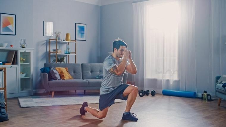 Allenamento gambe a casa, uomo che si allena sul pavimento del soggiorno