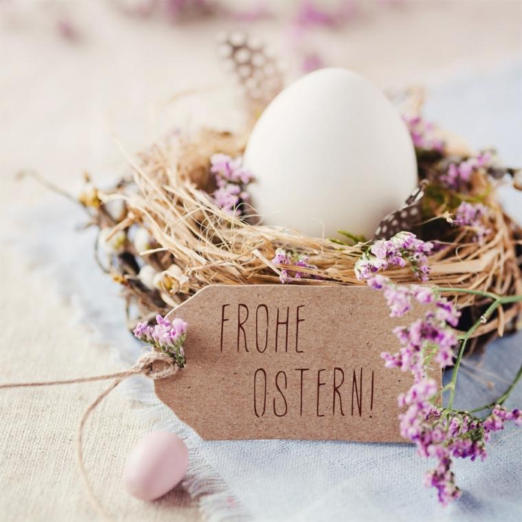 Cestino con un uovo bianco e fiori, bigliettino pasquale con scritta