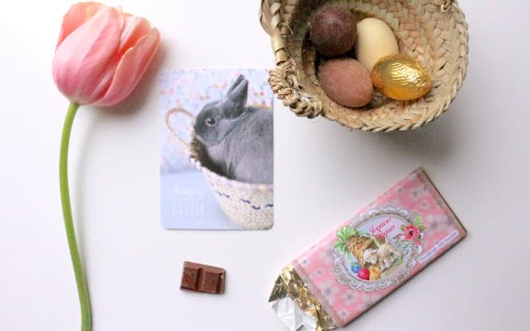 Foto di un tulipano con petali rosa, cestino con uova pasquali al cioccolato