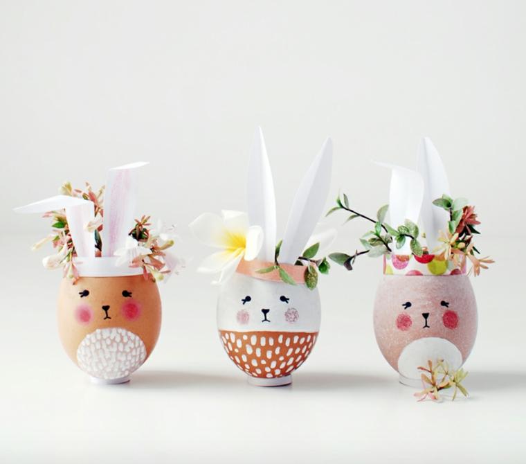 Tre gusci di uova con disegni di faccine, uova con fiorellini su sfondo bianco