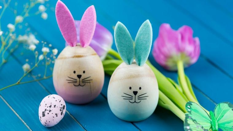 Foto di due uova pasquali con disegno faccine, tavola di legno blu con tulipani