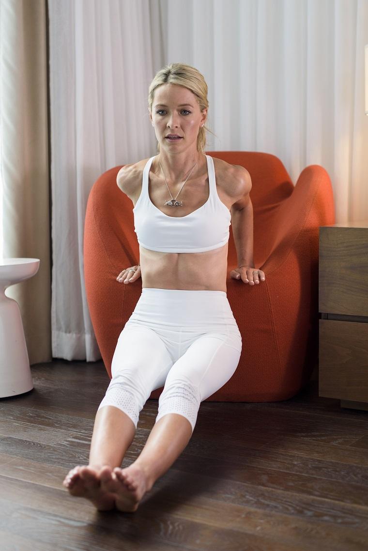 Allenamento a casa, donna che allena gli addominali sul divano di casa