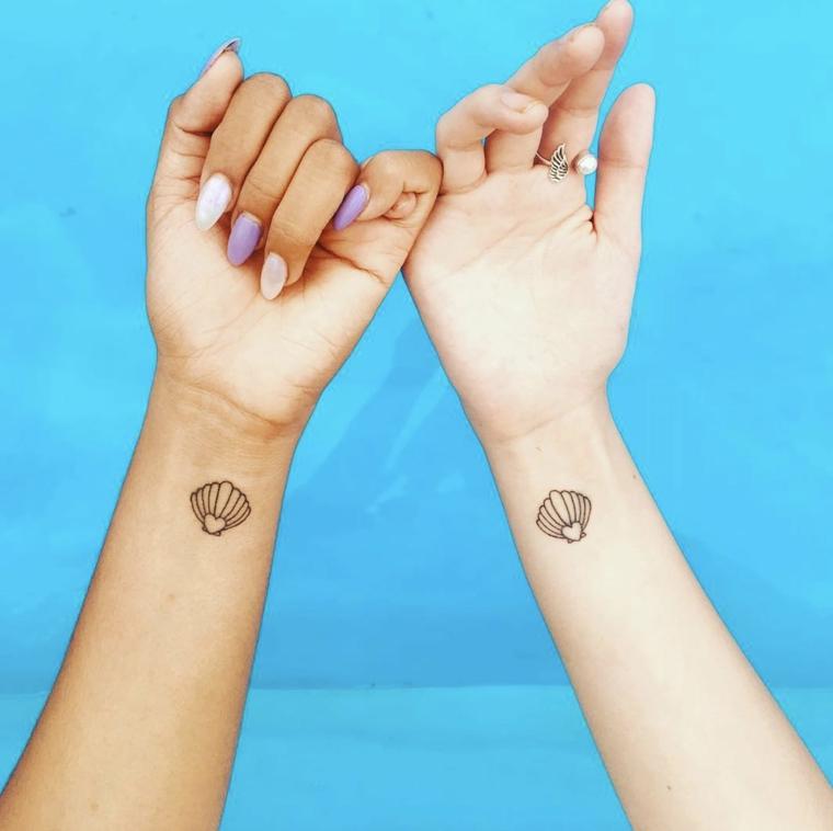 Tattoo sul polso della mano con disegno di una conchiglia, tattoo per due amiche