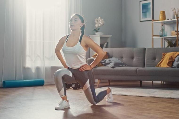 Donna che esegue affondi in avanti, allenarsi a casa donne, donna che si allena in soggiorno