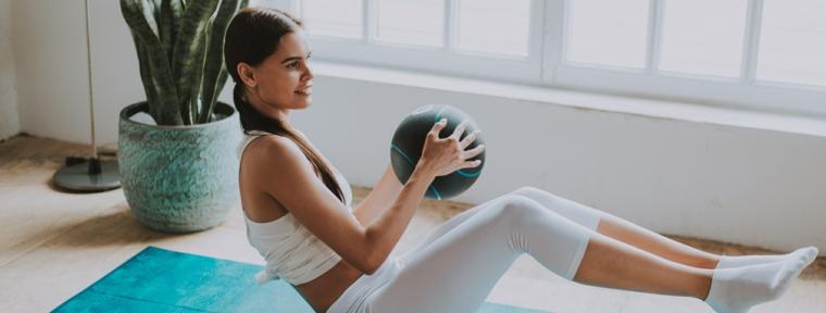 Allenamento gambe a casa, donna sul tappetino con palla in mano e gambe piegate