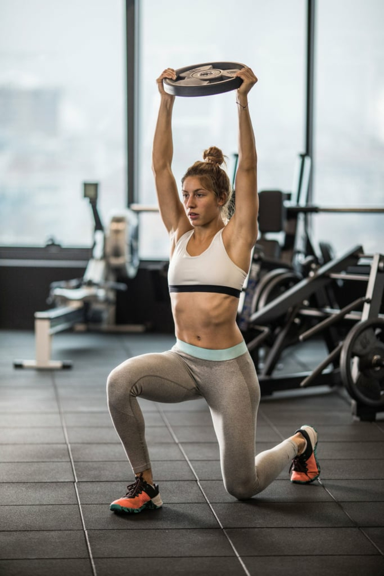 Esercizi gambe corpo libero, donna che allena le gambe con affondi e pesi in braccio