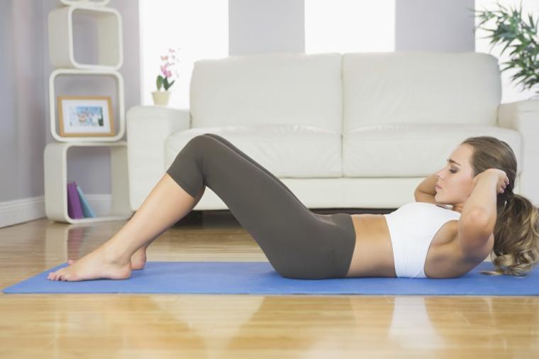 Donna che esegue esercizi per gli addominali sul tappetino, workout a casa