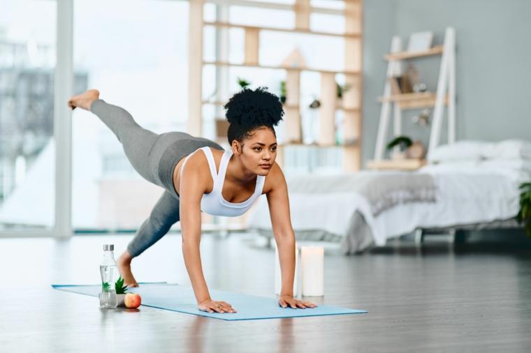Esercizi gambe corpo libero, donna che esegue esercizi per le gambe sul tappeto