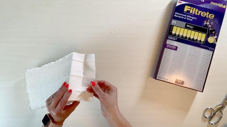 Mascherina antivirus fai da te, donna che taglia un filtro d'aria Hepa