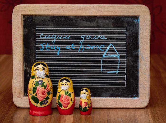 Bambole di legno russe con mascherina, lavagna con scritta e disegno di una casa