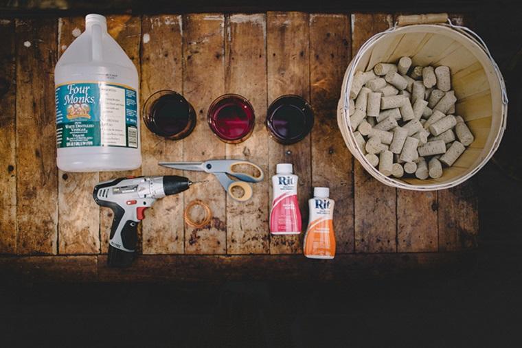 Idee con tappi di sughero, materiali posizionati su un tavolo di legno, pistola per colla calda e forbici