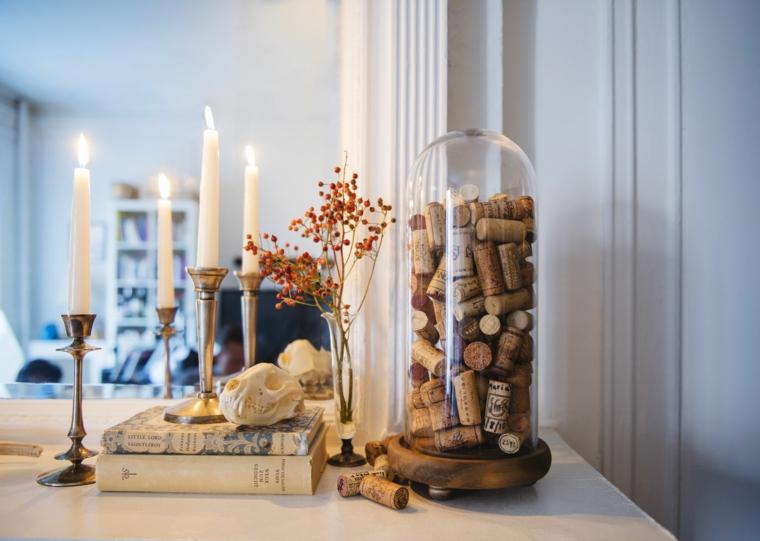 Contenitore con tappi di sughero, tavola con candele e due libri accanto