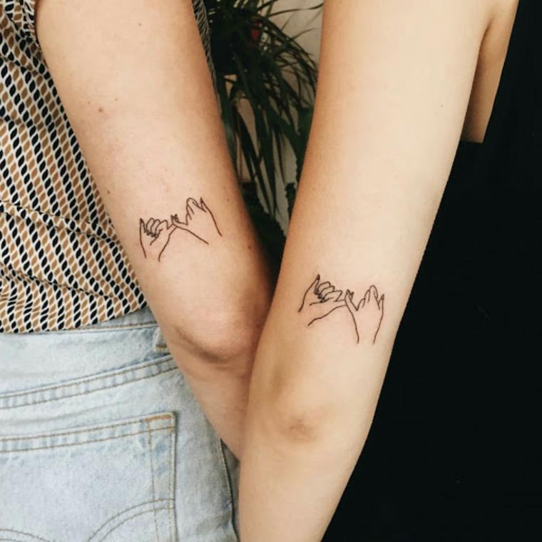 Tattoo sorelle, tatuaggio sul braccio con disegno mani unite di due ragazze