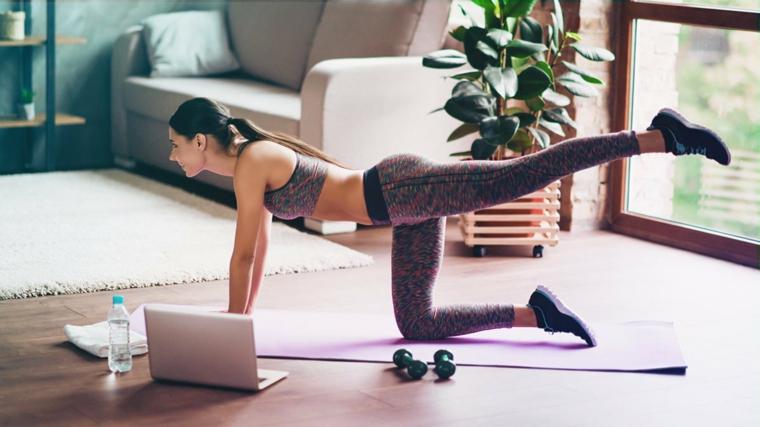 Esercizi gambe corpo libero, donna sul tappetino da ginnastica con gamba alzata