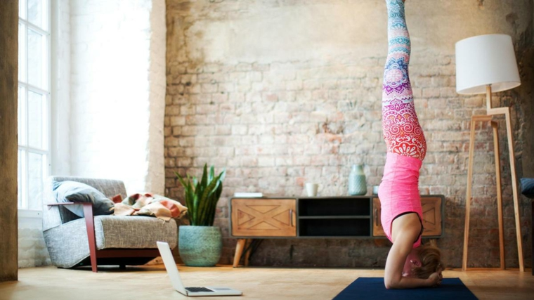 Allenamento a casa, donna sul tappetino con testa in giù in posizione di yoga