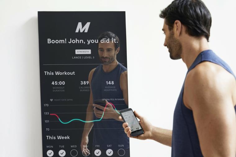 Scheda allenamento per aumentare massa muscolare a casa, uomo con telefono in mano