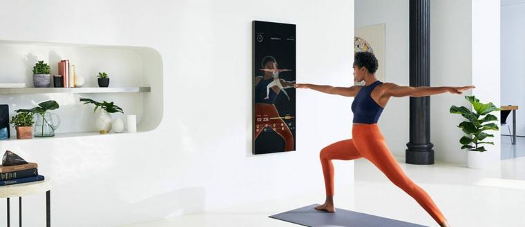 Donna che esegue esercizi di yoga sul tappetino, allenarsi a casa donne