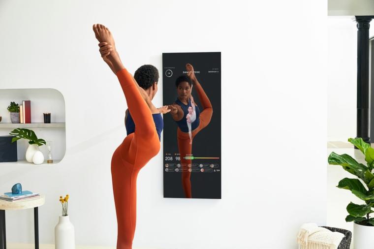 Allenamento a casa, donna che esegue esercizi, parete con uno specchio fitness