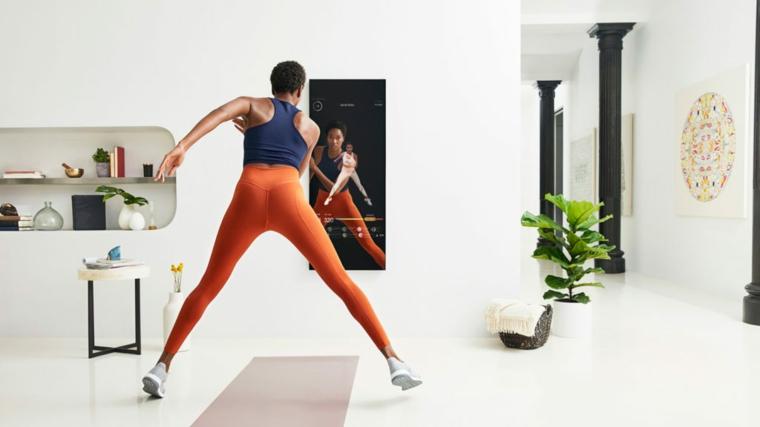 Esercizi gambe corpo libero, donna che si allena sul tappetino con fitness specchio