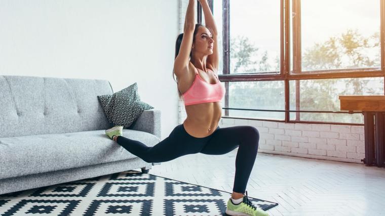 Allenamento completo a casa, donna che fa ginnastica sul divano del soggiorno