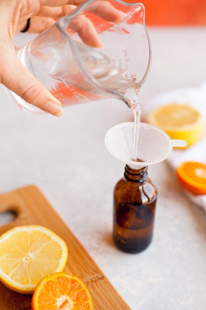 Tutorial disinfettante mani, donna che versa gli ingredienti in bottiglia di vetro