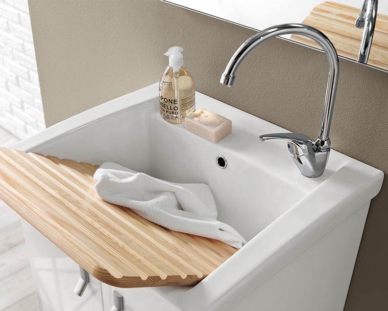 Lavanderia in casa, mobile lavabo in ceramica con asse da lavaggio in legno