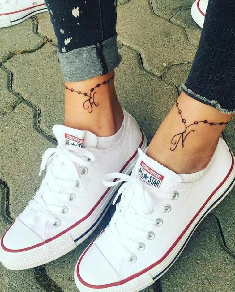 Tatuaggio sulla caviglia, tattoo di due amiche con iniziale, scarpe bianche e jeans abbinati