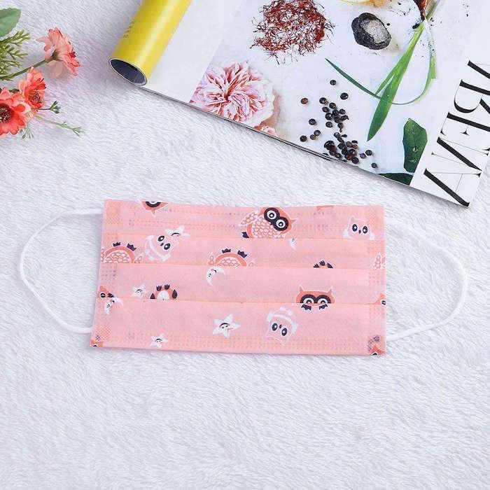 Una mascherina di colore rosa con disegni di gufo, tavolo con fiori e rivista